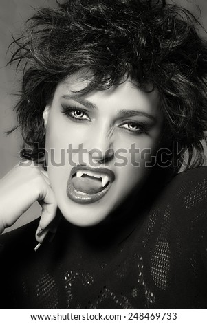 Black and white portrait of an attractive female vampire with light colored evil eyes baring her fangs at the camera in a Halloween concept - stock photo