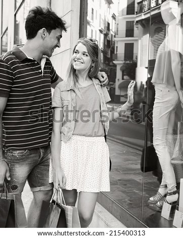 Black and white portrait of an attractive young couple on vacation city break together, looking at the fashion store shop windows smiling while shopping, outdoors. Consumer and travel lifestyle. - stock photo