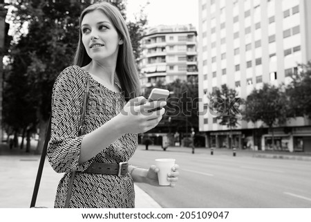 Black and white portrait of an attractive young professional business woman standing in a city street holding and using a smartphone on her way to work, turning back. Business technology on the go. - stock photo