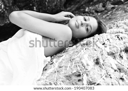 Black and white portrait of an attractive young woman laying on a coastal dark and textured rock mountain wrapped in a white sarong, sunbathing and relaxing during a summer holiday. Beauty lifestyle. - stock photo