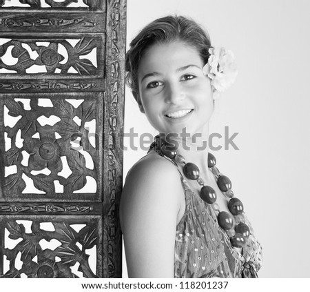 Black and white portrait of an attractive young woman wearing an exotic outfit and jewelry and leaning on a carved wood screen panel while on vacations at a health spa, smiling. - stock photo