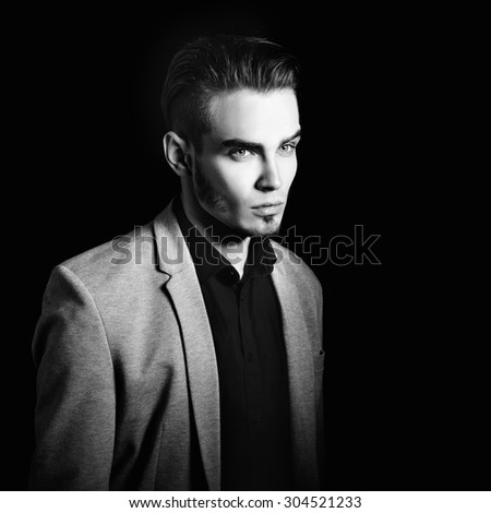 Black and white portrait of attractive mysterious young man over black background. - stock photo