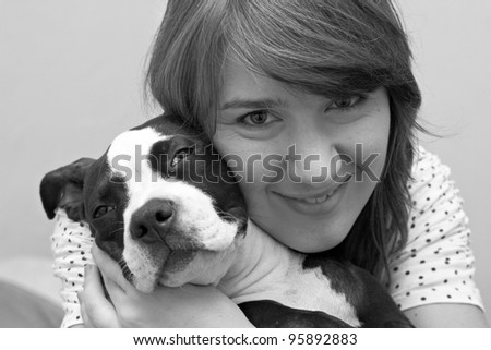 Black and white portrait of attractive young lady and sleeping Pit Bull puppy - stock photo