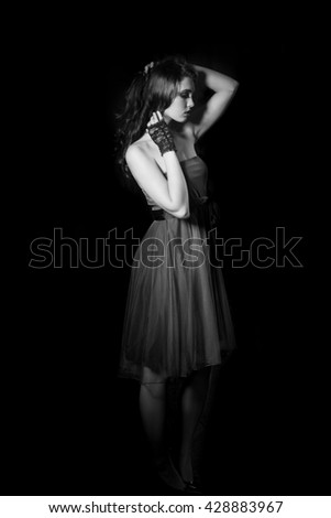 Black and white portrait of beautiful woman in strapless dress and lace gloves in dramatic glamor lighting. - stock photo