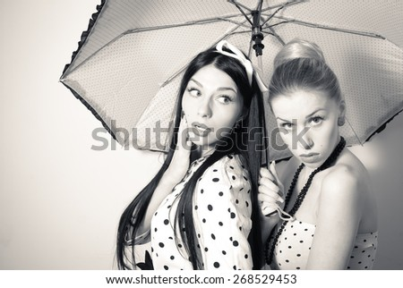 Black and white portrait of beautiful young women under umbrella looking surprised - stock photo