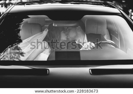 Black and white portrait of bride and groom kissing at car - stock photo