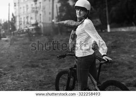 Black and White. Portrait of happy young bicyclist riding in park on her bike - stock photo