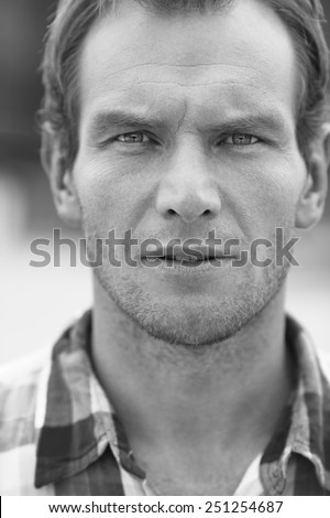 Black and white portrait of man in a checkered shirt. Outdoor shoot - stock photo