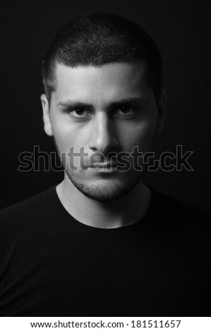 Black and white portrait of man in dark shirt - stock photo
