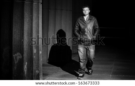 Black and white portrait of man in leather coat walking at night near columns - stock photo