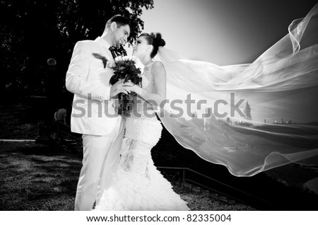 black and white portrait of newly married couple.wind lifting up long veil - stock photo