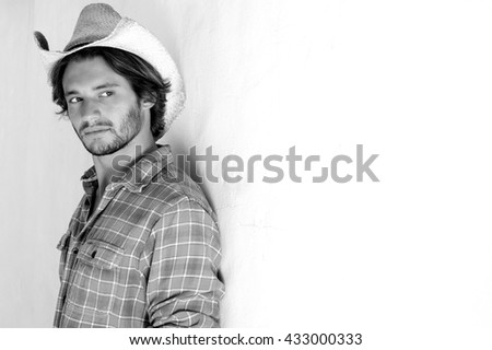 Black and white portrait of rugged young man looking serious in cowboy hat - stock photo