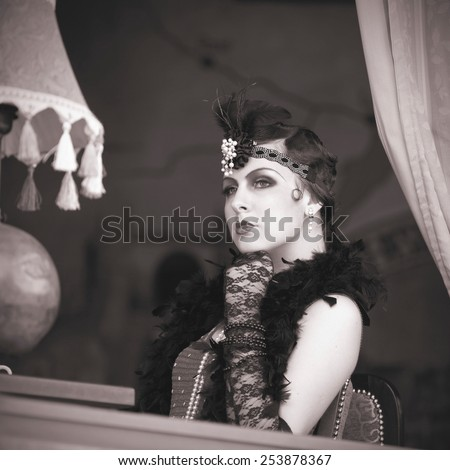 Black and White Portrait of The Beautiful Retro woman Sitting in the Cafe in Black Lace and Accessories in Style 1920s - 1930s  - stock photo