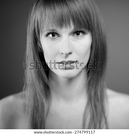 Black and white portrait of the beautiful young woman with long hair on dark background - stock photo