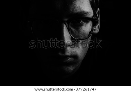 Black and white portrait of the young man in glasses in low key - stock photo