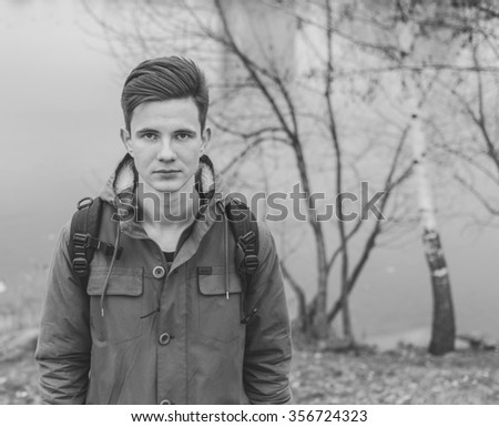 Black and white portrait of the young man on the river  - stock photo