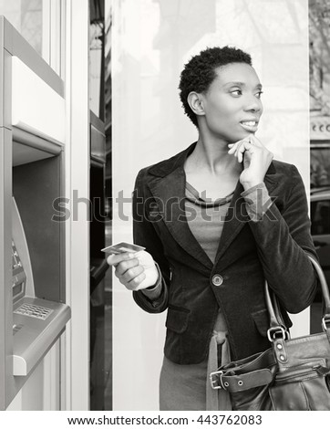 Black and white portrait of thoughtful beautiful african american business woman holding a credit card at a bank cash point, outdoors. Professional ethnic woman accessing funds in bank, lifestyle.  - stock photo