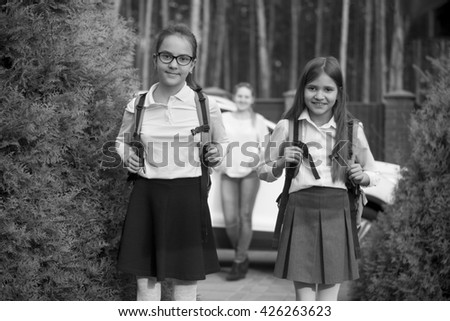 Black and white portrait of two cheerful girls going to school at morning - stock photo