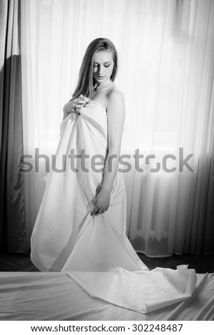 Black and white portrait of young beautiful lady hiding under white sheet standing on light window copy space background  - stock photo