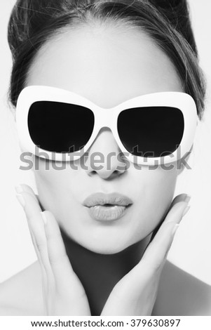 Black and white portrait of young beautiful woman in vintage sunglasses - stock photo