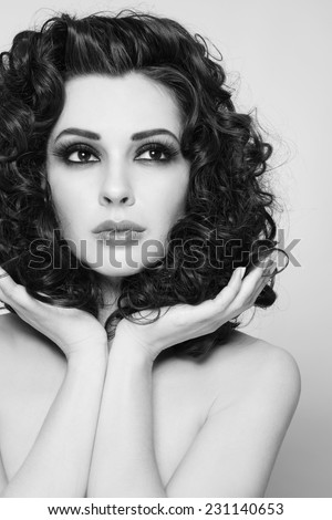 Black and white portrait of young beautiful woman with long healthy curly hair - stock photo