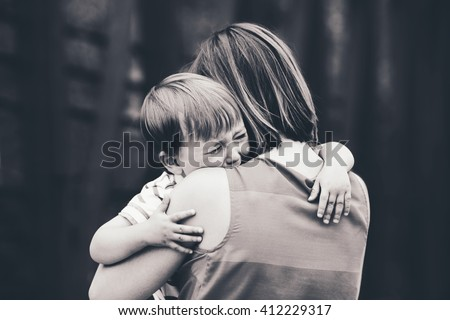 Black and white portrait of  young Caucasian woman mother comforting her crying little toddler boy son outside in park on summer day, parenthood lifestyle concept - stock photo