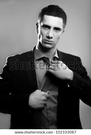 Black and white portrait of young handsome man untying tie - stock photo