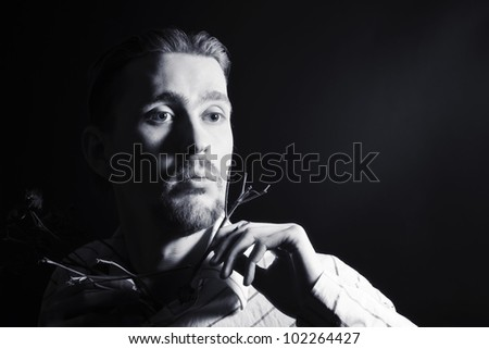 Black and white portrait of young trendy guy in the studio - stock photo