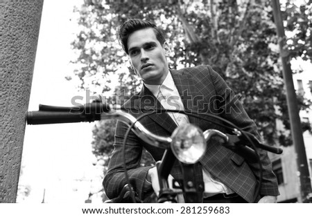 Black and white portrait on a young handsome businessman leaning on his bicycle  - stock photo