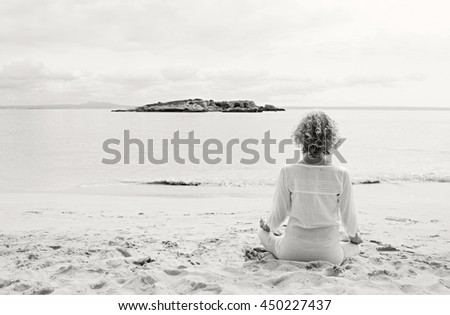 Black and white rear view of mature woman in holiday destination beach contemplating the sea sitting in yoga position, meditating outdoors. Well being sport and healthy lifestyle, nature exterior. - stock photo