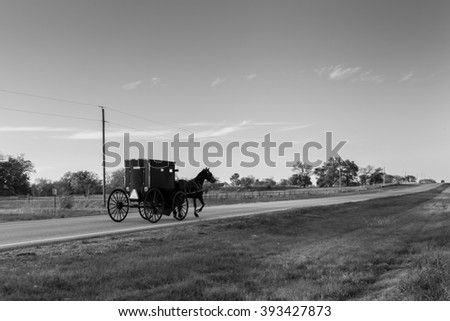 Black and White Rendering of a Horse and Buggy on a Rural Highway in Oklahoma Amish Country at Sunset - stock photo