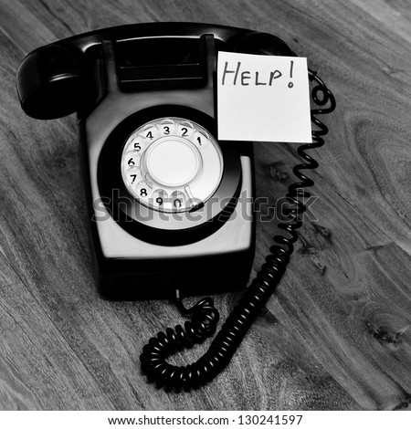 Black and white retro phone with customer service help note - stock photo