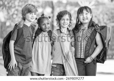 Black and white scene of happy children at school. - stock photo