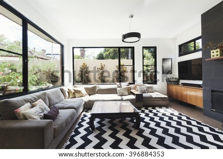 Black and white scheme living room with wood and grey tiling accents and chevron pattern floor rug - stock photo