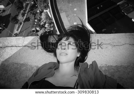 Black and white shot of beautiful young girl lying on building roof with the city in the background - stock photo