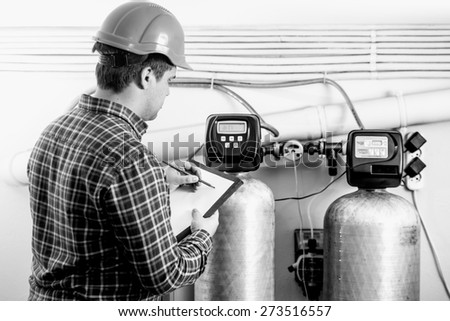 Black and white shot of male inspector checking factory equipment - stock photo