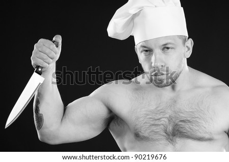 Black and white shot of shirtless chef with a kitchen knife, over a dark background - stock photo