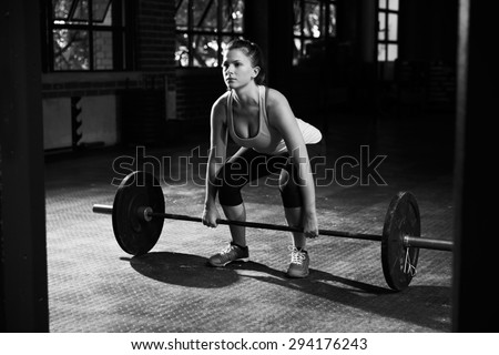 Black And White Shot Of Woman Preparing to Lift Weights - stock photo