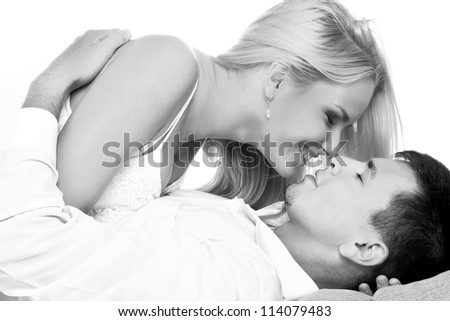 Black and white shot of young couple in love kissing - stock photo
