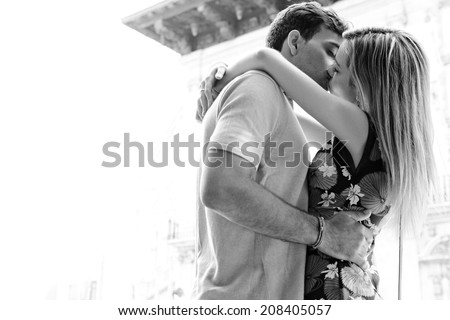 Black and white side view of a romantic young passionate couple kissing each other with passion in a city street during a sunny day on holiday, outdoors. (People, Lifestyle, Romance) - stock photo