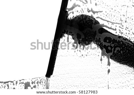 black and white silhouette of a window washer washing a window - stock photo