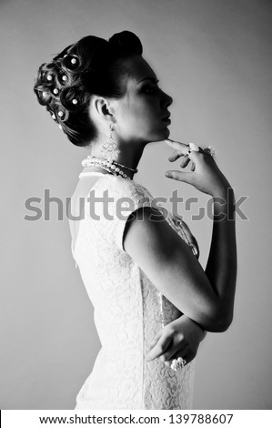 Black and white silhouette profile studio portrait of young pretty fashion bride model with elegant  dress, a lot of jewelry, beads and rings, holding her hands near her lips - stock photo