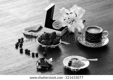 Black and white silver ring gift setting with morning coffee, dry dates, orange marmelade, blueberries and white lily flower - stock photo