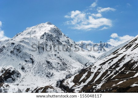 Black-and-white slope with serpentine road is against the mountains snow-covered and azure cloudy sky (the pass of Saint Bernard) - stock photo
