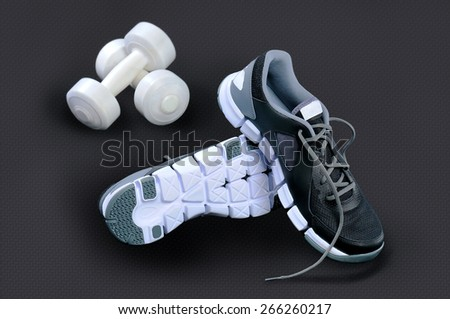 Black-and-white sneakers stand on heels concerning each other and white dumbbells lie against a dark background - stock photo