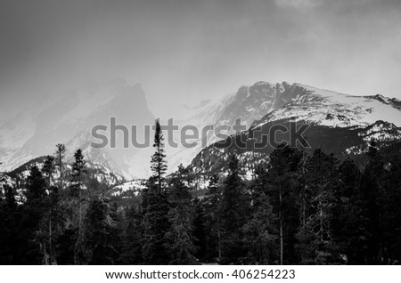 Black and white snow capped mountains covered by storm clouds. - stock photo