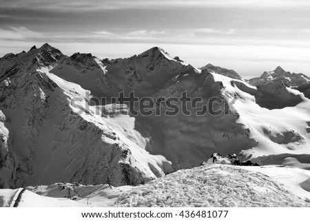 Black and white Snowy off-piste slopes at evening. Caucasus Mountains. View from ski slope of Mount Elbrus. - stock photo
