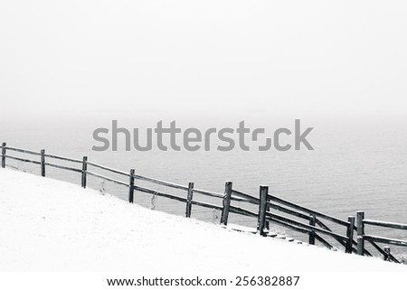 black and white snowy scene with a snow covered hillside and a fence running downward from left to right. lake in the background - stock photo