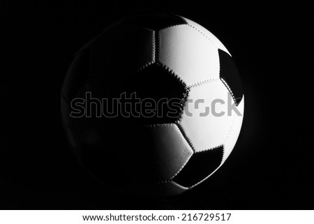 Black and white soccer ball in a dark blackground. - stock photo