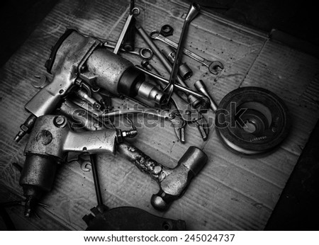 black and white spanner tools piled in workshop - stock photo